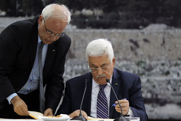 Palestinian Authority President Mahmoud Abbas (R) signs a request to join 15 United Nations and other agencies at his headquarters in the West Bank city of Ramallah on Tuesday, April 1, 2014 (photo credit: AFP/Abbas Monami)