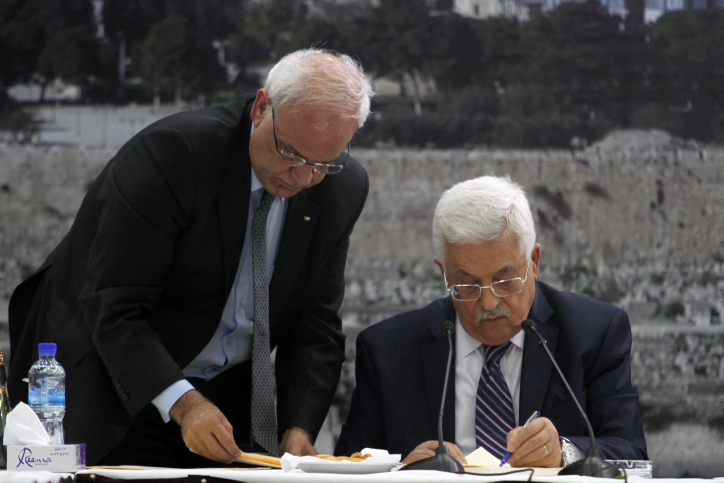 Palestinian Authority President Mahmoud Abbas, right, signs an application to UN and other international agencies, in the West Bank city of Ramallah, Tuesday, April 1, 2014. (photo credit: Issam Rimawi/Flash90)