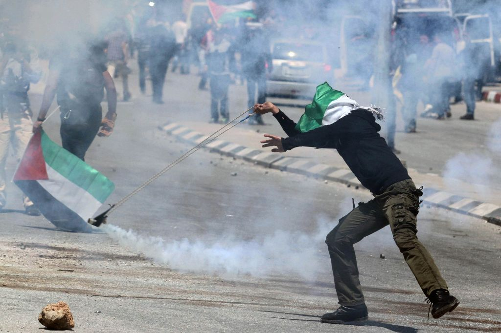 A Palestinian protester throws back a tear gas canister fired by Israeli soldiers during clashes outside the Ofer military prison near Ramallah, April 4, 2014. (photo credit: Issam Rimawi/Flash90)