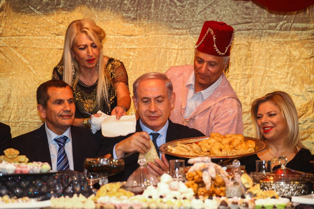 Prime Minister Benjamin Netanyahu, center, and his wife Sara attend the Jewish Moroccan celebration of Maimouna, in Or Akiva on April 21, 2014. (photo credit: Avishag Shaar Yashuv/Flash90/Pool)