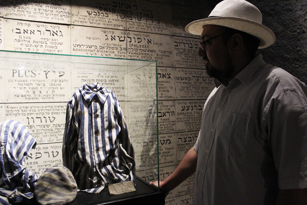 Ilan Goodman, curator at the Chamber of the Holocaust, points out a uniform from a concentration camp, one of the items housed at the chamber. (Photo credit: Rebecca McKinsey/The Times of Israel)