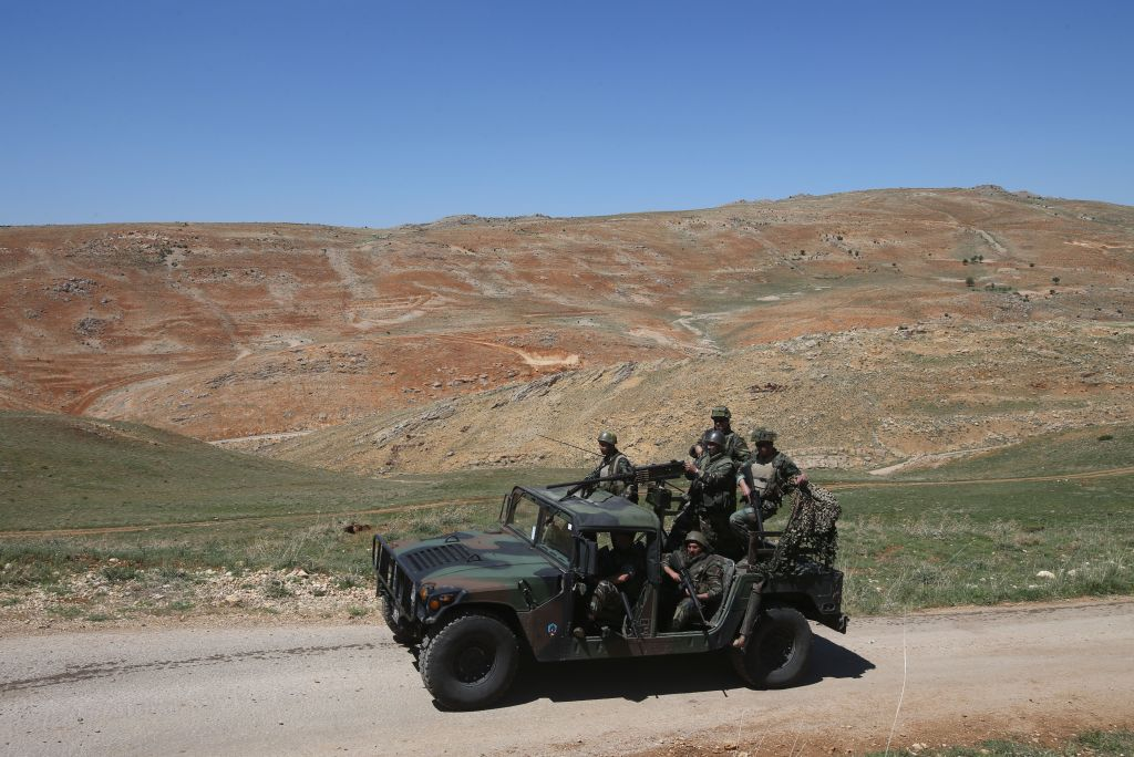In this picture taken on Tuesday, April 22, 2014, Lebanese army soldiers patrol a road near Ras al-Haref mountain at the unmarked Lebanese-Syrian border, eastern Lebanon. (photo credit: AP/Hussein Malla)