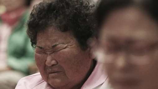 A local resident closes her eyes during a prayer to wish for safe return of passengers of