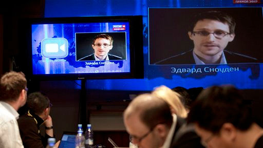 Edward Snowden, displayed on television screens, asks a question to Russian President Vladimir Putin during a nationally televised Q&A session, in Moscow, April 17, 2014. (photo credit: AP/Pavel Golovkin)