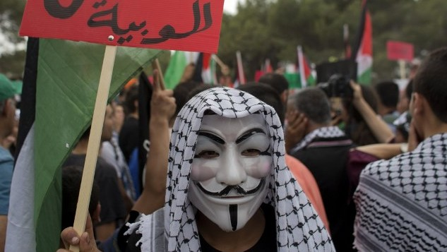 "An Arab Israeli wearing a Guy Fawkes mask and holding a placard that reads in Arabic ""Return"" takes part in ""The March of Return,"" May 6, 2014 (Photo credit: Ahmad Gharabli/AFP)"