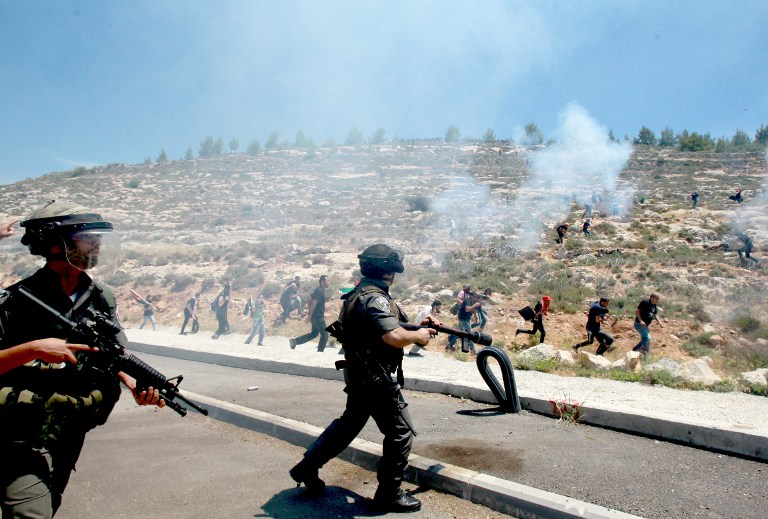 Israeli border police fire tear gas canisters during clashes with Palestinian protesters marking the 66th anniversary of the Nakba on Thursday, May 15, 2014, near the West Bank village of Walajah, south of Jerusalem (photo credit: AFP/Musa al-Shaer)
