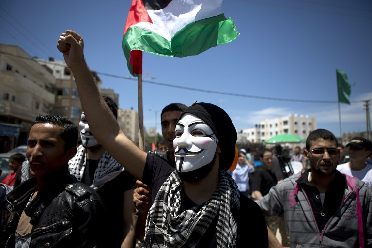 A Palestinian demonstrator, wearing a Guy Fawkes mask, takes part in a rally near the border with Israel, east of Gaza City, on May 15, 2014, to mark Nakba Day. (photo credit: AFP/Mohammed Abed)