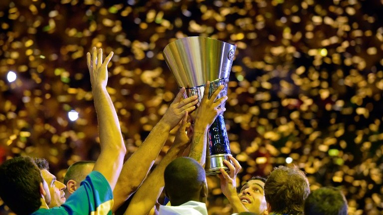 Maccabi Tel Aviv players gather around the trophy as they celebrate their victory after their Euroleague 2014 Gold medal Final Four basketball game on May 18, 2014 at the Mediolanum stadium in Assago. (photo credit: Olivier Morin/AFP)