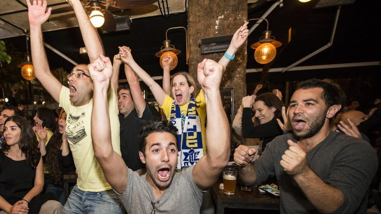 Maccabi Tel Aviv supporters watching the the Euroleague 2014 Final Four basketball match, Maccabi Tel Aviv vs Real Madrid, react to the victory of their team in a cafe on Kikar Rabin (Rabin Square) in Tel Aviv, May 18, 2014. (photo credit: Jack Guez/AFP)