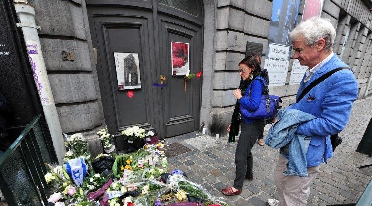 People pay their respects in front of a makeshift memorial at the entrance of the Jewish Museum in Brussels, on May 25, 2014 (photo credit: AFP/GEORGES GOBET)