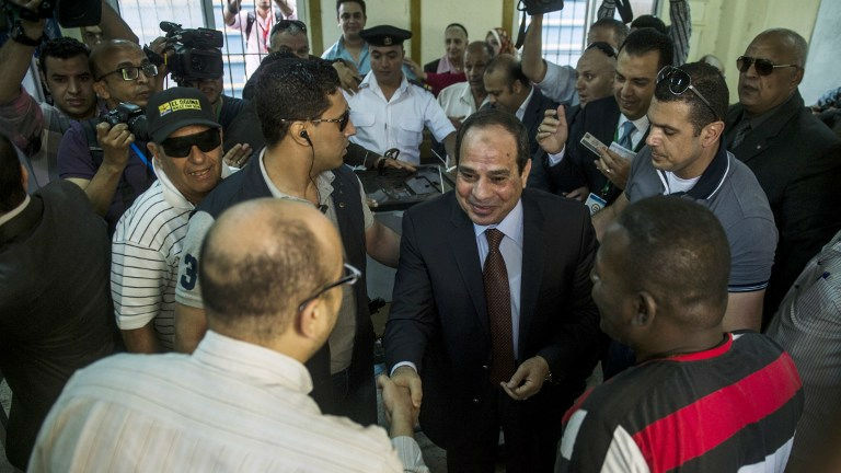Egypt's ex-army chief and leading presidential candidate Abdel Fattah al-Sisi (C) arrives at a polling station in Heliopolis to vote in Cairo on May 26, 2014 (photo credit: AFP/ Khaled Desouki)