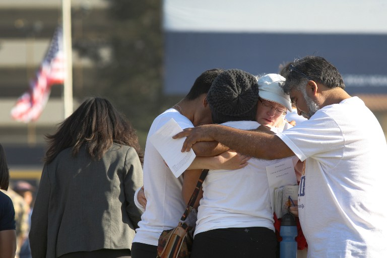 People hug at a public memorial service on the Day of Mourning and Reflection for the victims of a killing spree at University of California, Santa Barbara on May 27, 2014 in Isla Vista, California. (photo credit: AFP/David McNew/Getty Images)