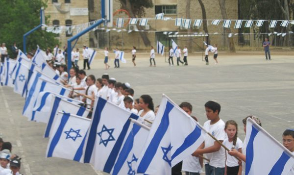 Children at the Efrata elementary school in Jerusalem march with Israeli flags.  Michele Chabin/JW