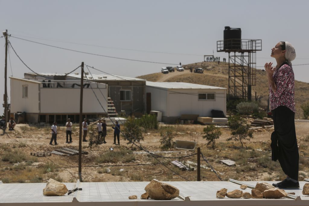 A settler prays atop her home during the demolition and evacuation of 10 structures in the Ma'ale Rehavam outpost in the West Bank, on Wednesday, May 14, 2014 (photo credit: Nati Shohat/Flash 90)