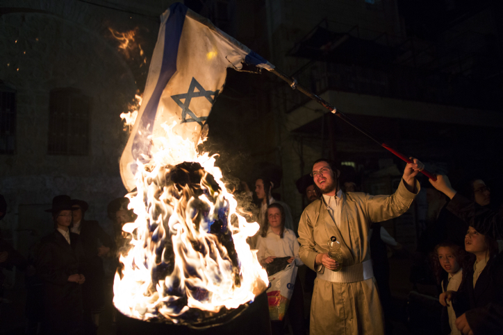 A member of the anti-Zionist group Neturei Karta burns the Israeli flag during celebrations marking the Jewish holiday of Lag B'Omer in the Ultra orthodox neighborhood of Mea Shearim in Jerusalem on May 17, 2014. (Yonatan Sindel/Flash90)