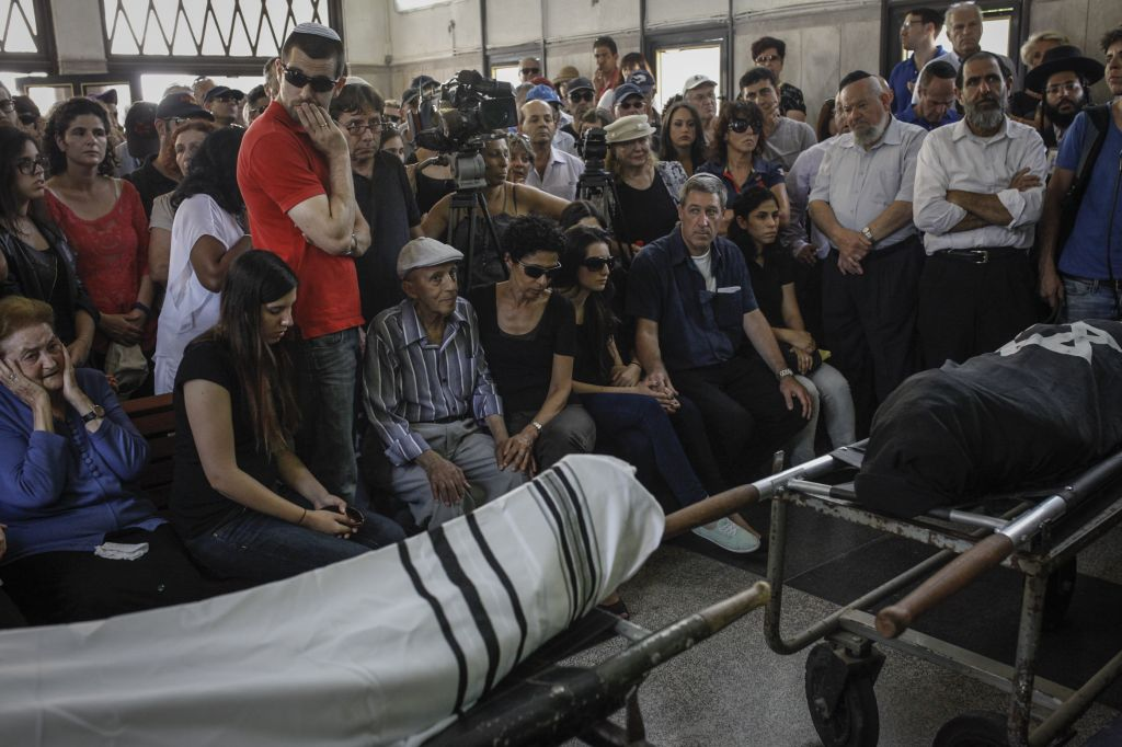 Relatives of Emmanuel and Miriam Riva attend the couple's funeral at the Kiryat Shaul cemetery in Tel Aviv, on Tuesday, May 27, 2014. (photo credit: Amir Levi/Flash90)