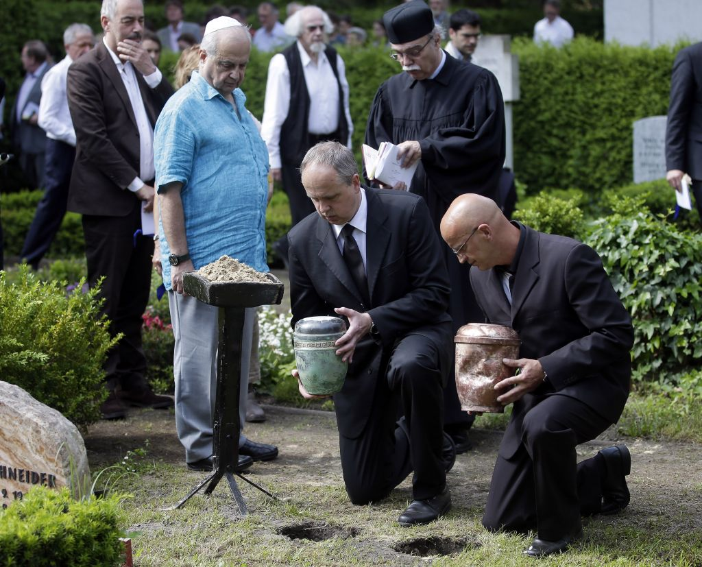 Alon Less, front left, attends the reburial of the urns of his father Avner Less and his mother Vera Less during a funeral service in Berlin, Germany, Friday, May 23, 2014. Avner Less, the man who interrogated Adolf Eichmann after he was brought to Israel, has been reburied together with his wife Vera in Wannsee, in the south of Berlin, on Friday. Less died in Switzerland in 1987 but was denied his wish to be buried in Hamburg alongside his wife Vera, who died in 1980. Now, after 34 years they are reunited in Berlin, not far from the place where the mass murder of Europe's Jews was agreed. (photo credit: AP Photo/Michael Sohn)