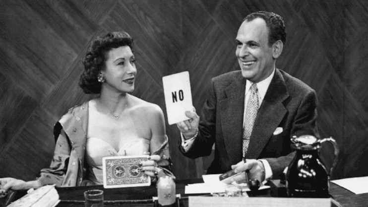 Photo of Arlene Francis and Moss Hart from an early television game show 'Answer Yes or No.' Hart was the host of the program and is seen revealing Francis' answer to a question. (NBC Television via wikipedia)