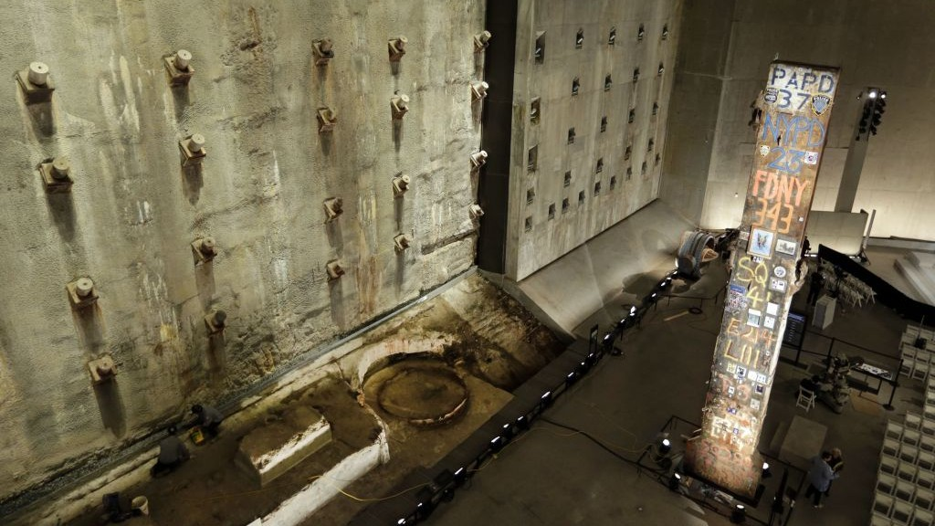 A portion of the World Trade Center slurry wall, left, and the symbolic last beam, are displayed at the National Sept. 11 Memorial Museum on Wednesday (photo credit: AP)