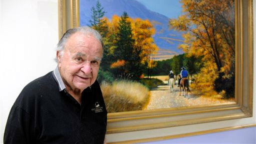 This June 2012 photo shows former 'Mad' magazine editor Al Feldstein standing near one of his paintings at Livingston HealthCare. Feldstein, whose 28 years at the helm of Mad magazine transformed the satirical publication into a pop culture institution, has died, T