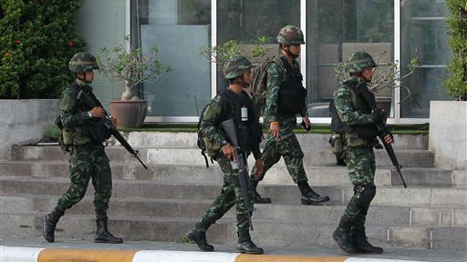 Thai soldiers walk outside the National Broadcasting Services of Thailand (NBT) building Tuesday, May 20, 2014 in Bangkok, Thailand (photo credit: AP /Apichart Weerawong)
