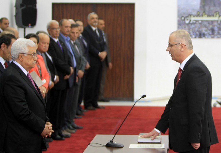 Palestinian Prime Minister Rami Hamdallah (R) is sworn in along with the new Palestinian unity government in the presence of PA President Mahmud Abbas (L) in the West Bank city of Ramallah, Monday, June 2, 2014 (photo credit: AFP/ABBAS MOMANI)