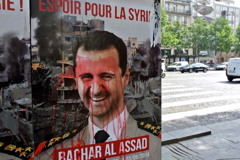 A poster mocking Syrian president Bashar al-Assad is seen on the Champs Elysees avenue in Paris, on June 2, 2014, a day before the presidential election in Syria.  (Photo credit: AFP Photo/Ammar Abd Rabbo)