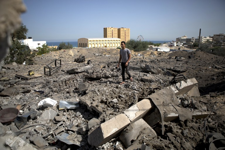 A Palestinian man walks on the rubble past a crater following an air strike by the Israeli Air Force on Gaza City, on Monday, June 16, 2014 (photo credit: AFP/MOHAMMED ABED)
