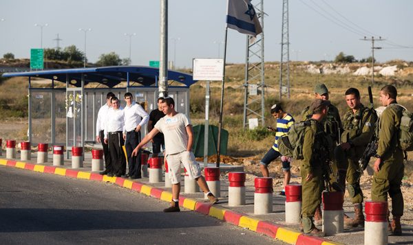 Israeli soldiers guard the roadside hitchhiking area at the Gush Etzion junction in the West Bank. Flash 90