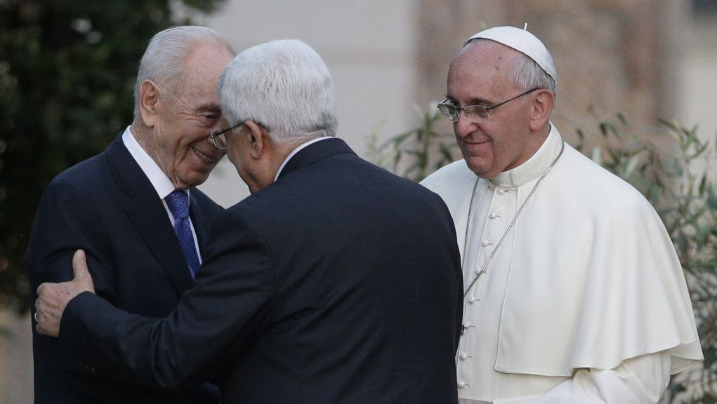 Pope Francis looks on as Israel's President Shimon Peres, left, and Palestinian Authority President Mahmoud Abbas greet each other during an evening of peace prayers in the Vatican gardens, Sunday, June 8, 2014. (photo credit: AP Photo/Gregorio Borgia)