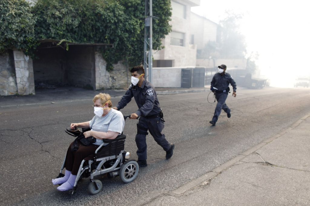 Firefighters evacuate residents from apartment buildings as a large fire rages near Jerusalem's Ein Kerem neighborhood, Wednesday, June 25, 2014 (photo credit: Yonatan Sindel/FLASH90)