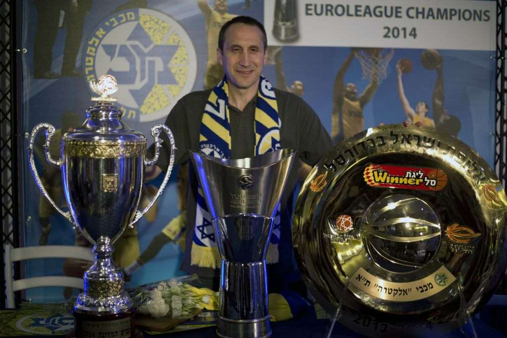 Maccabi Tel Aviv's head coach David Blatt poses for photographers with the Israeli cup, European club champions cup and the Israeli club champions trophy after a news conference in Tel Aviv, Israel,Thursday, June 12, 2014. (photo credit: AP/Ariel Schalit)