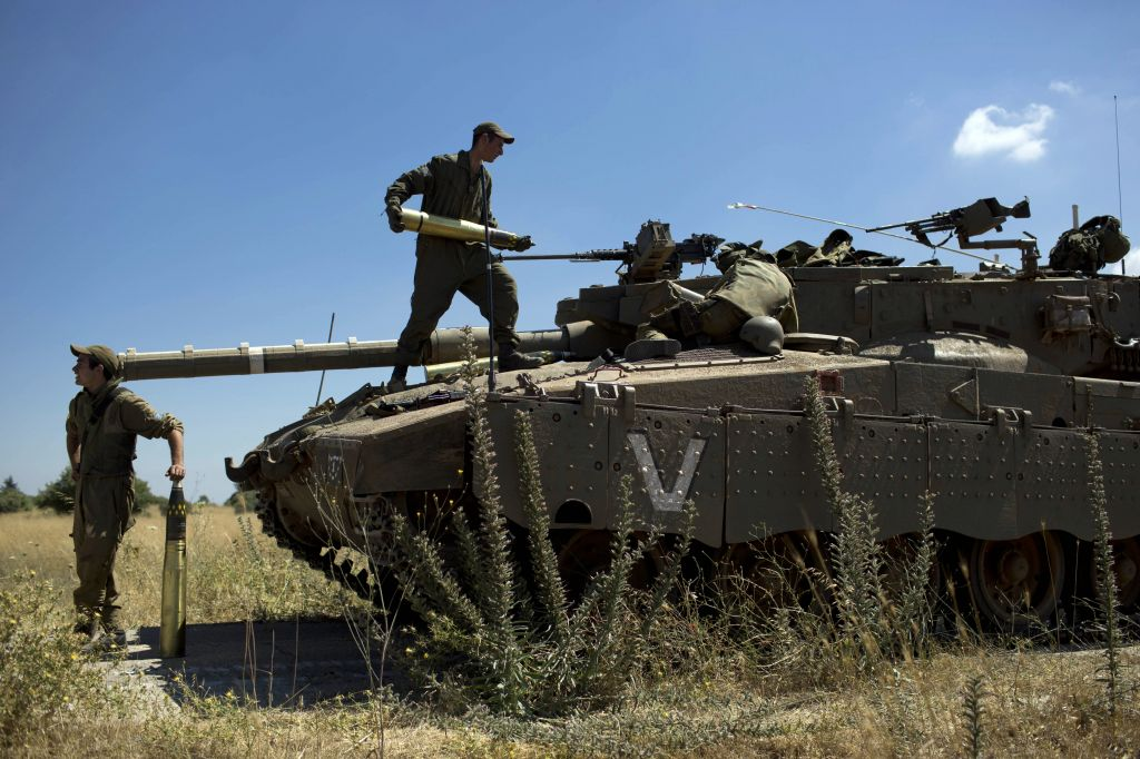 Israeli soldiers load shells into their tank following the first death on the Israeli side of the Golan since the eruption of the Syrian civil war more than three years ago, near the Israeli village of Alonei Habashan, June 22, 2014 (photo credit: AP/Oded Balilty)