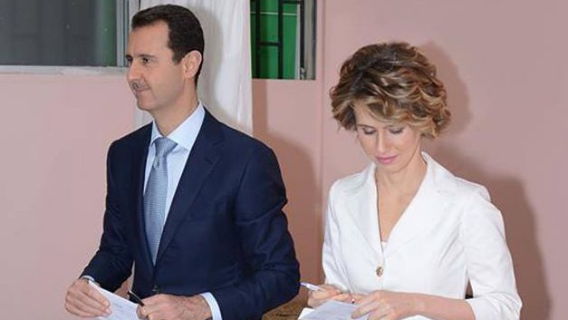 In this photo released by the Syrian official news agency SANA, Syrian President Bashar Assad, left, and first lady Asma Assad, right, leave a voting booth to cast their vote at a polling center, in Damascus, Syria, Tuesday June 3, 2014.(Photo credit:AP/SANA)