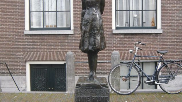 A statue of Anne Frank in front of the house in which she hid from the Nazis. Wikimedia Commons