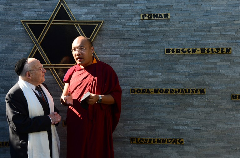 Rabbi Tovia Ben-Chorin (L), leader of Berlin's Jewish community, chats with the 17th Karmapa Ogyen Trinley Dorje (R) following talks at a Synagogue in Berlin on June 7, 2014 (photo credit: AFP/JOHN MACDOUGALL)