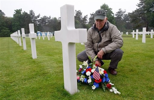 Paul Clifford, 70, from Boston, US, places flowers on the grave of Walter J. Gunther Jr, the uncle of his best friend, in the Normandy American Cemetery and Memorial, in Colleville sur Mer, France, Wednesday June 4, 2014. (photo credit: AP/Claude Paris)