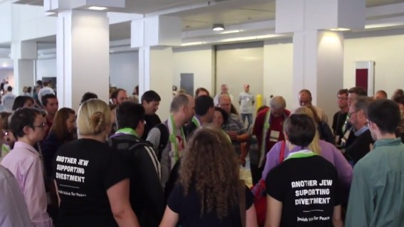 Several attendants of the Presbyterian General Assembly in Detroit form a prayer circle and sing for Israeli-Arab peace. Two are seen wearing shirts which read: 'Another Jew supporting divestment.' (screen capture: YouTube)