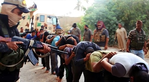 This image posted on a militant website on Saturday, June 14, 2014, which has been verified and is consistent with other AP reporting, appears to show militants from the al-Qaida-inspired Islamic State of Iraq and the Levant (ISIL) leading away captured Iraqi soldiers dressed in plain clothes after taking over a base in Tikrit, Iraq. (Photo credit: AP Photo via militant website)