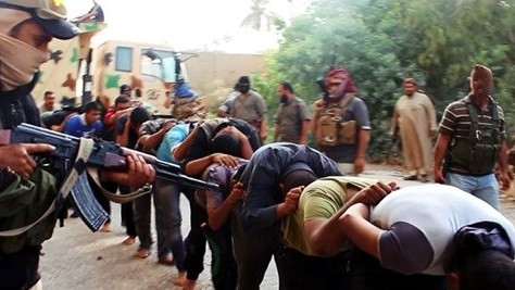 This image posted on a militant website on Saturday, June 14, 2014, which has been verified and is consistent with other AP reporting, appears to show Islamic State militants leading away captured Iraqi soldiers dressed in plain clothes after taking over a base in Tikrit, Iraq. (Photo credit: AP Photo via militant website)