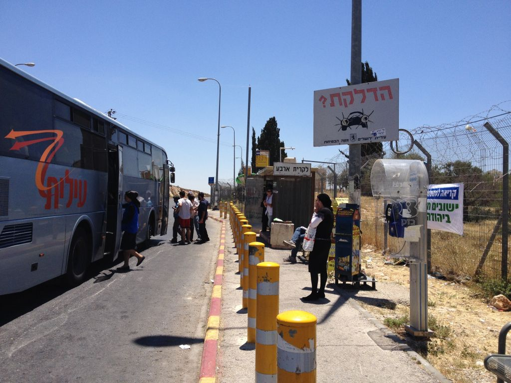 A public bus pulling up at the trempiada, while others continue to wait for other options in the hot sun (photo credit: Jessica Steinberg/Times of Israel)