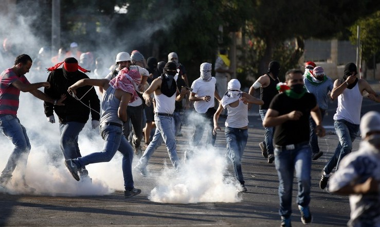 Palestinian protesters stand amid smoke after Israeli forces fired tear gas during clashes in Shuafat, East Jerusalem on July 4, 2014. (Photo credit: AFP/ THOMAS COEX)