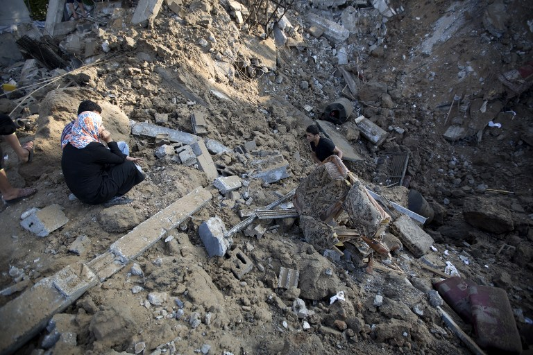 A Palestinian man removes a piece of furniture from the rubble of a home which police said was destroyed in an Israeli air strike in Beit Hanoun, in the northern of Gaza Strip on July 9 2014.  (photo credit: AFP/MOHAMMED ABED)