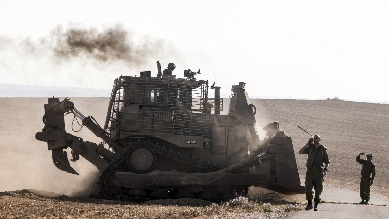 An Israeli D9 bulldozer rolls along the southern Israeli border with the Gaza Strip following Israeli airstrikes on the Gaza Strip on July 10, 2014. (photo credit: Jack Guez/AFP)