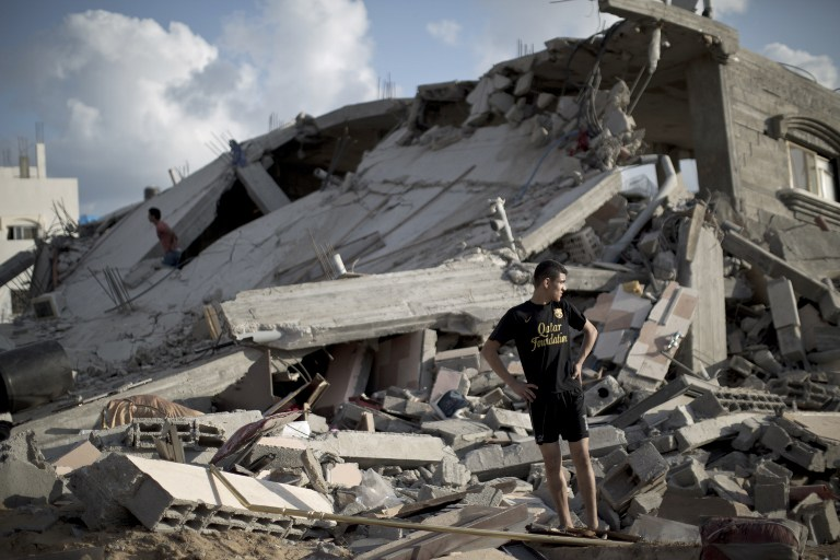A Palestinian man stands on the rubble of a destroyed building following an Israeli strike on Beit Lahiya, in the northern Gaza Strip on July 15, 2014.  (photo credit: AFP/MAHMUD HAMS)