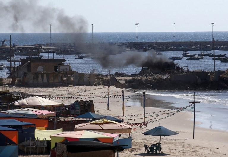 Smoke billows from a beach shack following an Israeli military strike, on July 16, 2014 in Gaza City which killed four children (photo credit: AFP/THOMAS COEX)