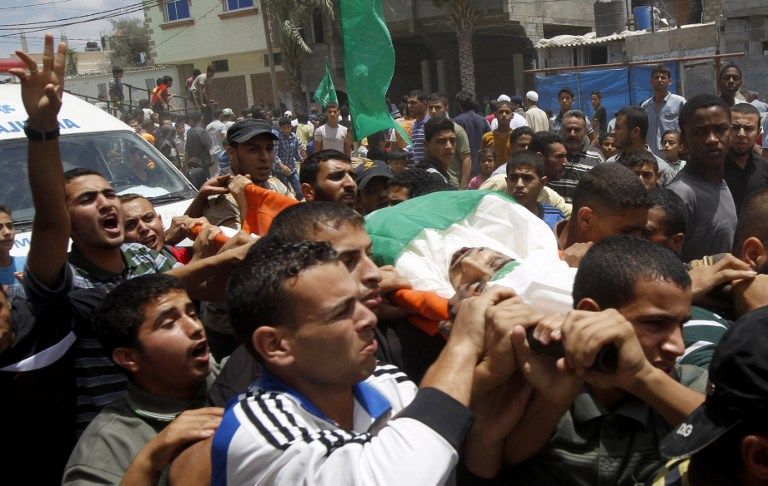 Palestinian mourners carry the body of 20-year-old Hamas fighter Bashir Abdel Aal during his funeral in the southern Gaza Strip town of Rafah on July 17, 2014, after he was killed by tank shelling (photo credit: AFP/SAID KHATIB)