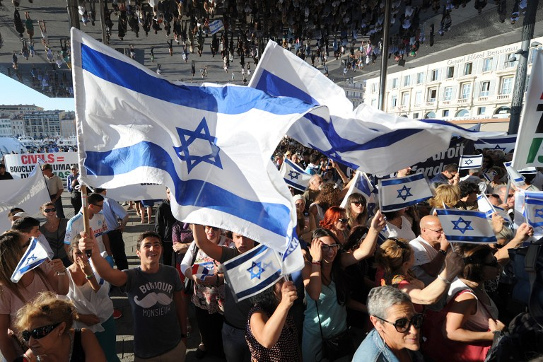 People wave Israeli flags as they take part in a demonstration supporting Israel on July 27, 2014 in Marseille, southeastern France. (photo credit: AFP PHOTO / BORIS HORVAT)