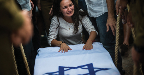 A woman mourns over the casket of Israeli soldier Jordan Bensimon Tuesday in Ashkelon. Getty Images