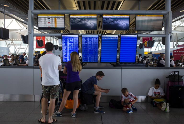 People stand in the Delta Airlines terminal at John F. Kennedy Airport July 22, 2014 in New York City after the Federal Aviation Administration halted all flights from the US to Tel Aviv. ( photo credit: Eric Thayer/Getty Images/AFP)